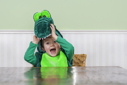 image of child wearing dinosaur costume